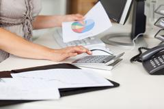 Businesswoman holding piechart while using calculator at desk Stock Photos