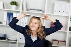 businesswoman with laptop on head clenching teeth - stock photo