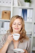 businesswoman holding coffee cup in office - stock photo