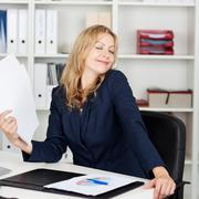 businesswoman fanning herself with documents at desk - stock photo