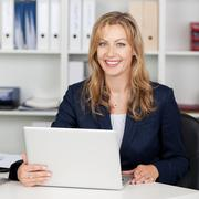 smiling businesswoman using laptop at office desk - stock photo