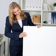 businesswoman with white billboard in office - stock photo