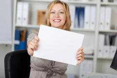 smiling businesswoman holding blank paper - stock photo