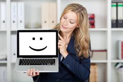 businesswoman displaying smiley face on laptop's screen - stock photo