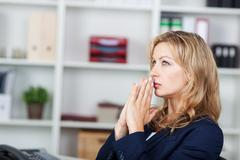businesswoman with hands clasped looking away in office - stock photo