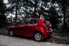 A red chevrolet sonic along a dirt road. Stock Photos