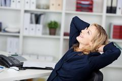 Businesswoman relaxing with hands behind head at desk Stock Photos
