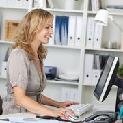 businesswoman using computer at desk in office - stock photo