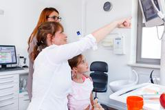 A doctor showing a young family a x-ray picture on led monitor Stock Photos