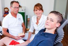 counseling session  in a dentistry surgery with a young boy and two doctors - stock photo