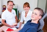 Stock Photo of counseling session  in a dentistry surgery with a young boy and two doctors