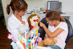 a dentistry woman doctor plays brushing teeth with a young girl - stock photo