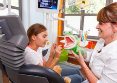a dentistry doctor plays with a young girl - stock photo