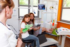 A dentistry doctor looks the client mother a child. Stock Photos