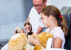 a doctor explains a young teenager girl how she tcan care the teeth - stock photo