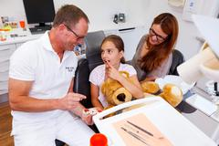 a doctor explains a young family, mother and teenager girl, how she can care  - stock photo