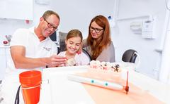 a doctor explains a young family how they can care the teeth - stock photo
