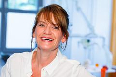 Portrait of a smiling woman doctor in a dental surgery Stock Photos