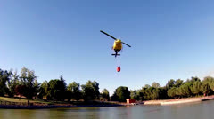 Fire rescue heavy helicopter with water bucket, goes to a fire. Stock Footage