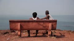 GOA, INDIA, 4 JANUARY 2013: TWO OLD MEN SIT ON BENCH. TOP SEA VIEW. Stock Footage