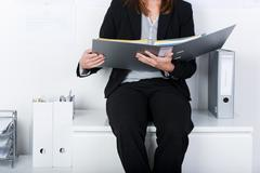 Businesswoman holding binder while sitting on counter Stock Photos