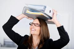 Happy businesswoman placing binders on head in office Stock Photos