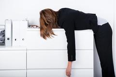 businesswoman sleeping on counter - stock photo