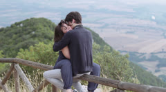 Stock Video Footage of loving couple kissing sitting on a fence in the mountains,caresses