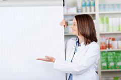 smiling female pharmacist presenting a flip-chart - stock photo