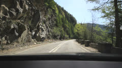 Driving on a mountain road in a conifer forest near a rock wall Stock Footage