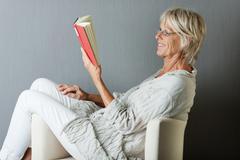 Happy senior woman reading a book sitting on sofa Stock Photos