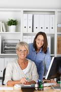 two females smilingly posing inside the office - stock photo