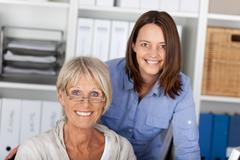 Young and old generation posing in office Stock Photos