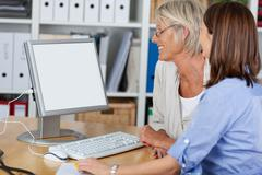 two females looking at the computer - stock photo