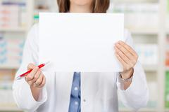 Pharmacist holding pen while displaying blank paper in pharmacy Stock Photos