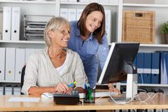businesswomen using computer at desk - stock photo