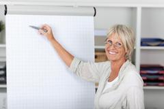 senior businesswoman pointing with felttip pen on presentation b - stock photo
