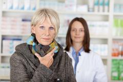 Unwell senior woman in sweater with pharmacist in background Stock Photos