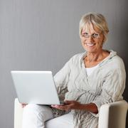 senior woman with laptop sitting on couch against grey wall - stock photo