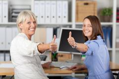 businesswomen gesturing thumbs up at desk - stock photo