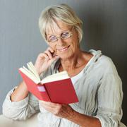 Senior woman reading novel against grey wall Stock Photos