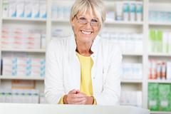 female pharmacist smiling while leaning on counter in pharmacy - stock photo