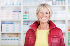 female pharmacist wearing jacket while smiling in pharmacy - stock photo