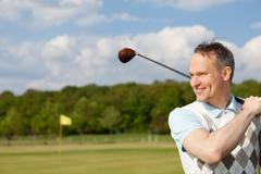 happy man practising golf - stock photo