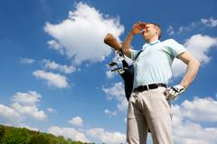 Golfer against blue sky Stock Photos
