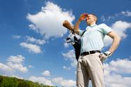 Stock Photo of golfer against blue sky