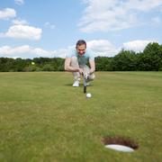 Golfer aiming at golf course Stock Photos