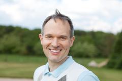 Mature man smiling at golf course Stock Photos