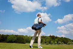 Stock Photo of mature male golfer carrying bag on course
