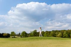 man playing golf at course - stock photo